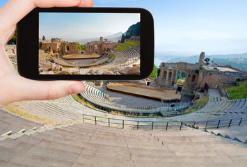tourist taking photo of ancient amphitheater