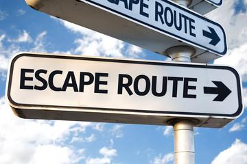 Escape Route direction sign on sky background