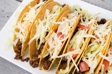 Ground beef tacos with cheese lettuce and tomatoes against woode