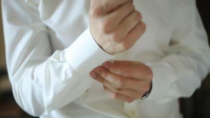 groom dress shirt and buttoning cuffs