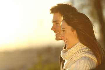 Happy couple looking at sunset in winter