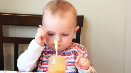 little girl independently eats fruit puree