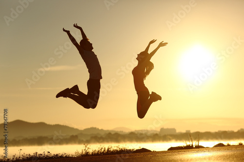 Leinwandbild Motiv Fitness couple jumping happy at sunset