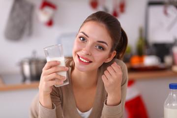 Smiling attractive woman having breakfast in kitchen interior