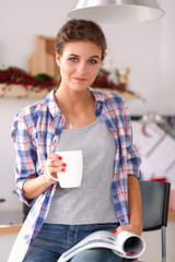 Woman reading mgazine In kitchen at home