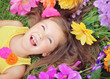 Happy little girl crown laying on the grass with flowers