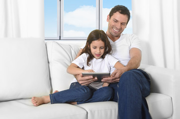 father on couch with sweet little daughter using digital tablet