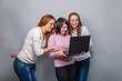 Three girls girlfriends, looking laptop on a gray background