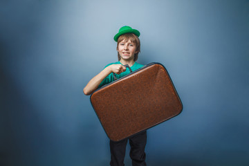 European-looking boy of ten years with a  suitcase in hat  on