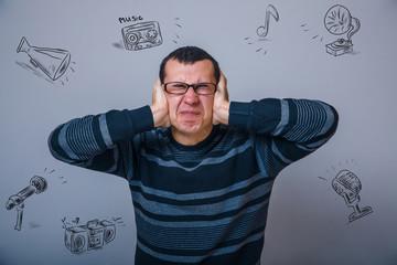 European man of thirty years in glasses closes her ears loud