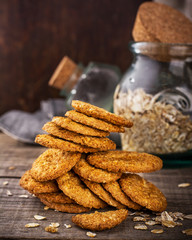 Thin oatmeal cookies crackers on a wooden dark background