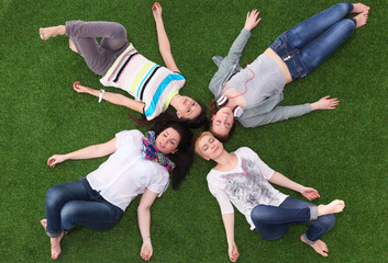 group of smiling friends lying on grass in circle
