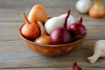Sweet onions and dried husk in a bowl on wooden boards
