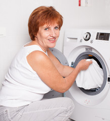 Woman puts clothes in the washing machine