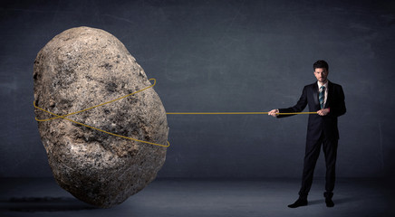 Businessman pulling huge rock with a rope