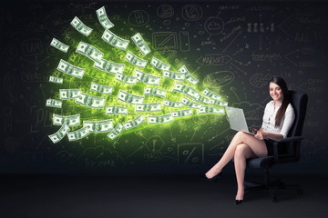 Businesswoman sitting in chair holding laptop with dollar bills