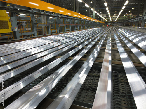 Aluminum lines on a conveyor belt in a factory. - 79379738