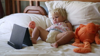 little girl lies in bed among toys and watches cartoons