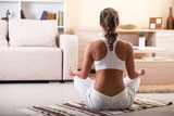 Young female meditate in her living room.