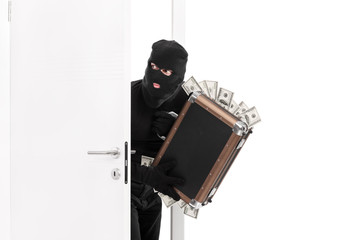Thief with a bag full of money entering a room