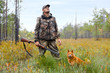 hunter with a gun and a dog on the swamp - 79384543