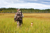 hunter with a dog crosses the swamp