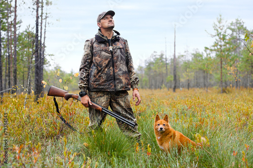 Fotobehang Jacht hunter with a gun and a dog on the swamp