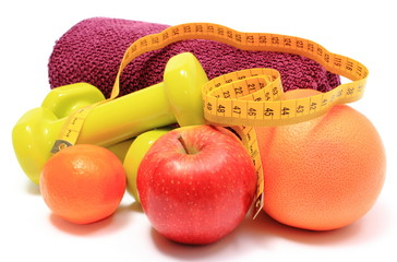 Fruits, tape measure, green dumbbells and towel on white