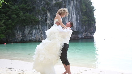 strong groom lifts blonde bride arm round waist over himself aga