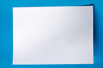 White piece of paper over a blue background.
