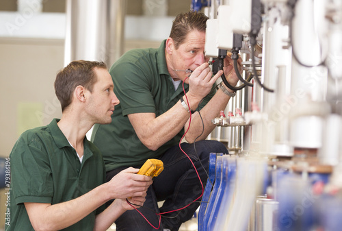 Two male technician repairing agriculture machinery.. - 79386196