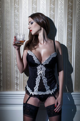 Sexy woman in corset with whiskey