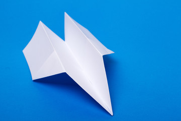White paper plane over a blue background.
