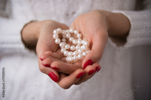 Pearls in female hands - 79388150