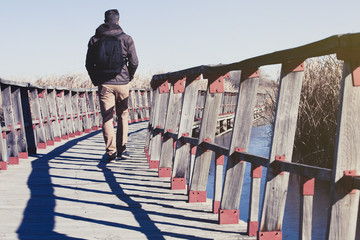 Man walking over a wood bridge in the nature, with a backpack.