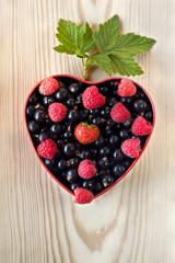 raspberries, black currants in a bowl