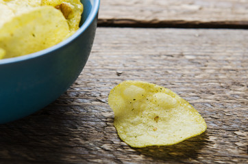 chips with herbs in blue bowl on a wooden table