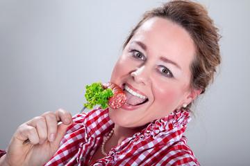 Junge Frau genießt Salami Stück auf Gabel
