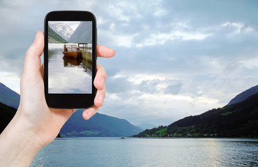 tourist taking photo of fjord in Norway in evening