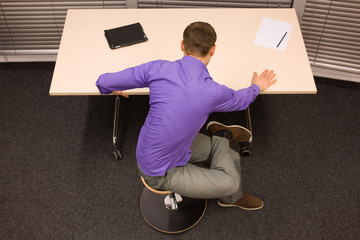 man exercising during short breake in work at his desk in office
