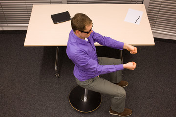 man exercising  at his desk in office