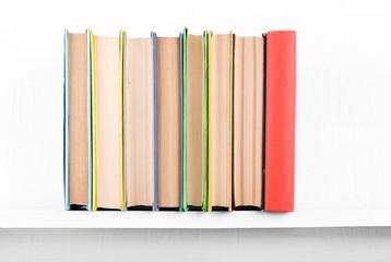 Old books on bookshelf on white wall background