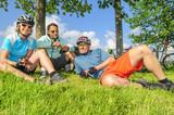 Drei Radler relaxen in der Wiese
