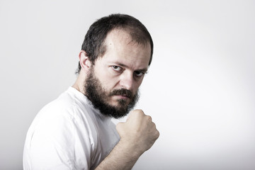 Young man with beard, showing fist, ready to fight