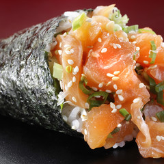 A close up of salmon temaki against a red background