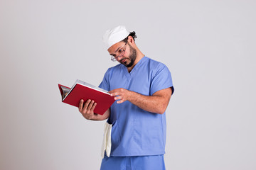 Young Doctor in Clinical Outfit is Reading a Patient Diagnose