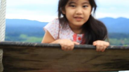 Little Asian child enjoy on swing in the park
