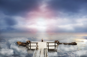 Woman sitting on an old pier in the sky