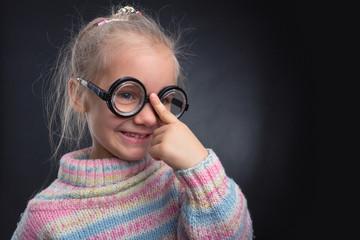 Little girl in glasses makes faces
