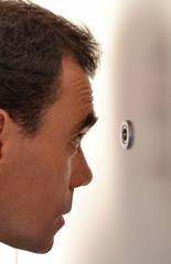 Hombre espiando a través de mirilla de puerta.